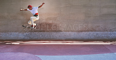 Buy stock photo Shot of a young man doing tricks on his skateboard at the skatepark