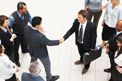 Buy stock photo High angle view of Partners shaking hands while surrounded by colleagues