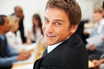 Buy stock photo Happy executive looking at you with colleagues at work in background