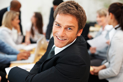 Buy stock photo Smiling executive looking at you with colleagues having discussion in background