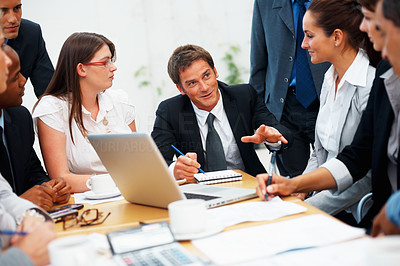 Buy stock photo Handsome business man explaining project to colleagues during meeting