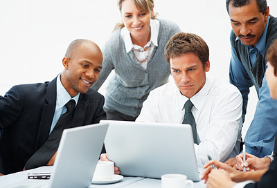 Buy stock photo Executive looks at laptop while colleagues look over his shoulder