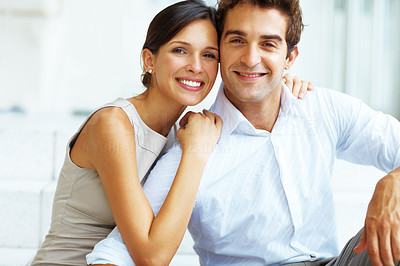 Buy stock photo Portrait of a affectionate young couple sitting together and smiling