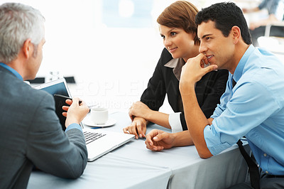 Buy stock photo Focus on two executives listening with mature business man explaining work on laptop