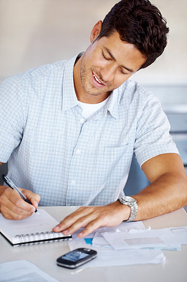 Buy stock photo Portrait of a young handsome casual businessman taking note in a notepad at office