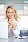 Pretty businesswoman sitting at her desk looking happy