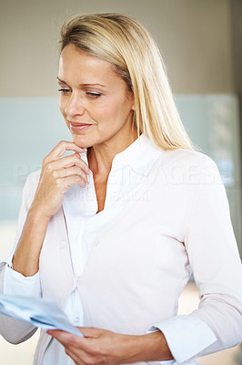 Buy stock photo Portrait of a thoughtful young businesswoman holding some paper in hand