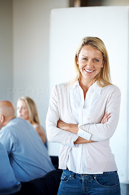 Buy stock photo Portrait of a smart young businesswoman standing with folded hand her colleagues in background
