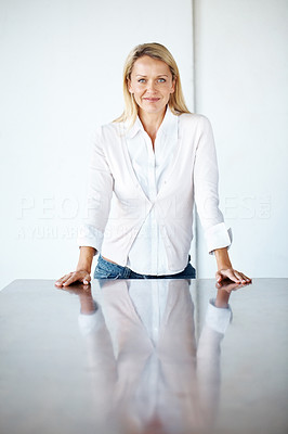 Buy stock photo Portrait of a smart businesswoman standing near conference table at office