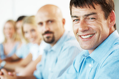 Buy stock photo Closeup of a happy mature businessman siting in a meeting with his colleagues in office