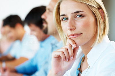 Buy stock photo Closeup of a thoughtful young business woman sitting in a meeting with her colleagues