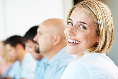 Buy stock photo Portrait of a pretty young businesswoman smiling in a meeting with her associates in background