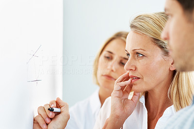 Buy stock photo A mature businesswoman addressing an issue on the whiteboard alongside colleagues