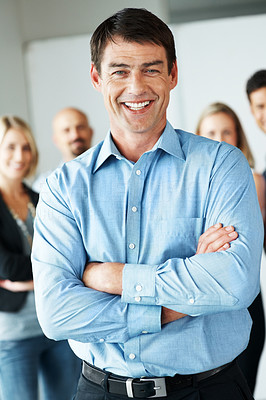 Buy stock photo Portrait of a handsome businessman with his business colleagues in background