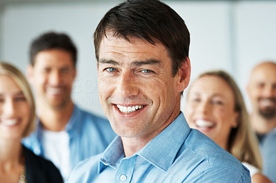 Buy stock photo Closeup portrait of a confident businessman smiling with his team in background