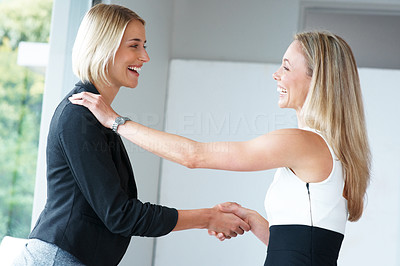 Buy stock photo Portrait of a happy young businesswoman handshaking after striking a business deal at office