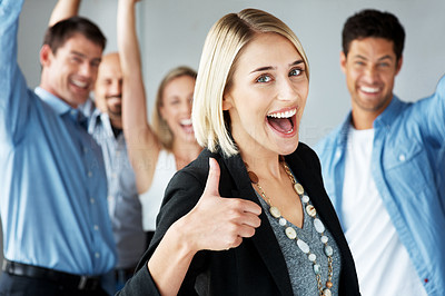 Buy stock photo Excited young business woman showing thumbs up with happy team in background