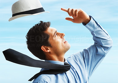 Buy stock photo Businessman with wind knocking hat of his head on blue background