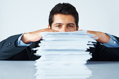 Buy stock photo Attractive businessman looking over the top of a stack of papers
