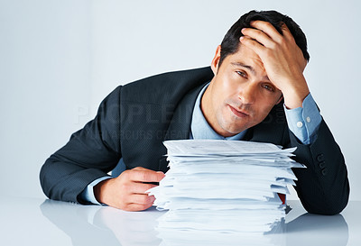 Buy stock photo Business man with hand on head sitting behind stack of papers