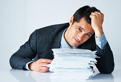 Buy stock photo Frustrated businessman with hand in hair and sitting behind stack of papers