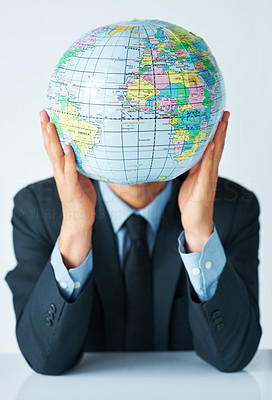 Buy stock photo Business man holding up globe in front of face