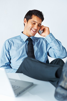 Buy stock photo Businessman smiling while on the phone in front of laptop