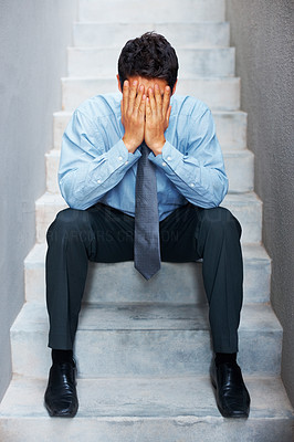 Buy stock photo A disappointed executive sitting sorrowfully on the steps with his head in his hands