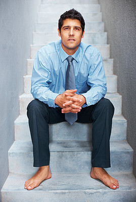 Buy stock photo Thoughtful business man sitting on steps barefoot