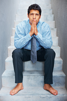 Buy stock photo Barefoot businessman deep in thought