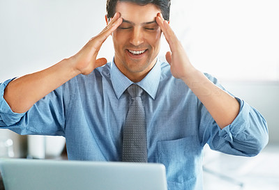 Buy stock photo View of man holding fingers to his temples with laptop in front of him