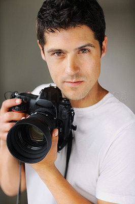 Buy stock photo Male photographer holding his professional camera