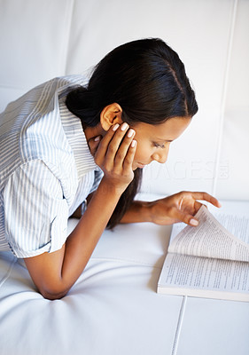 Buy stock photo Attractive woman lying down, reading a book