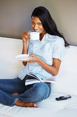 Buy stock photo Pretty woman sitting on sofa drinking cup of tea