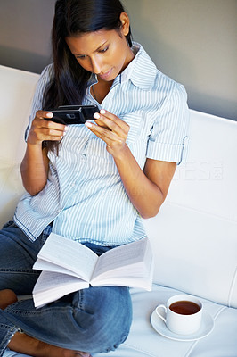 Buy stock photo Pretty woman sitting on her sofa reading a text message on her phone