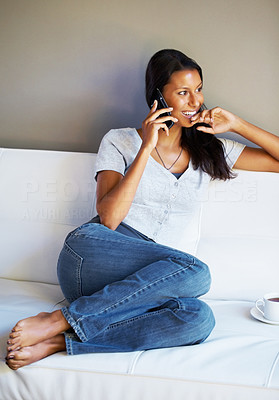 Buy stock photo Pretty woman sitting on sofa and talking on phone