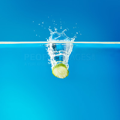 Buy stock photo View of cucumber slice dropping in water against blue background