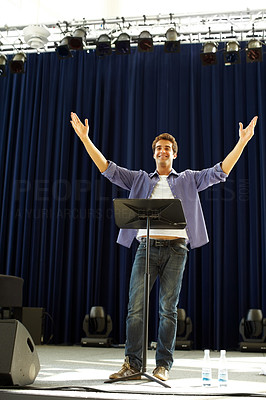 Buy stock photo Portrait of happy young guy performing on stage with his hands raised smiling confidently