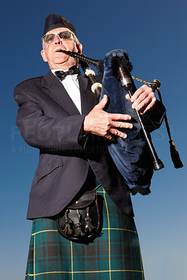 Buy stock photo Mature highlander wearing kilt and playing bagpipes against blue sky