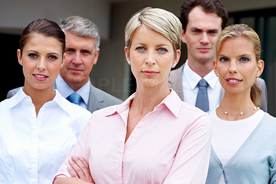 Buy stock photo Young female business executive looking confidently with her staff in background