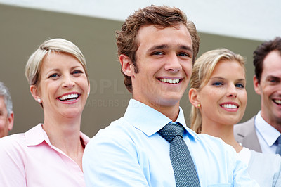Buy stock photo Portrait of a handsome young businessman smiling with his staff in background