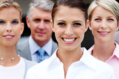Buy stock photo Pretty young business woman smiling with her coworkers in background