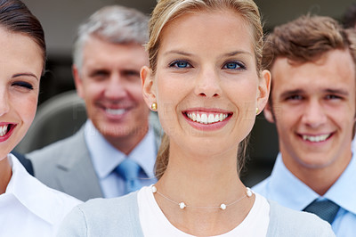 Buy stock photo Successful young female executive smiling with her staff in background