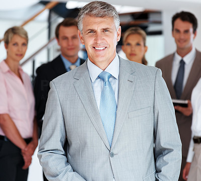 Buy stock photo Successful business man standing with his staff in background at office