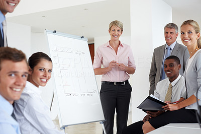 Buy stock photo Happy young business woman giving a presentation to her coworkers during a meeting at the office