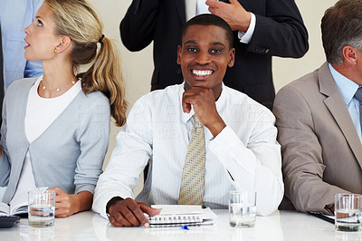 Buy stock photo Confident young afroamerican businessman smiling at a meeting with associates
