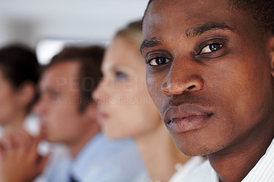 Buy stock photo Closeup of a young afroamerican businessman looking confidently with his associates in background