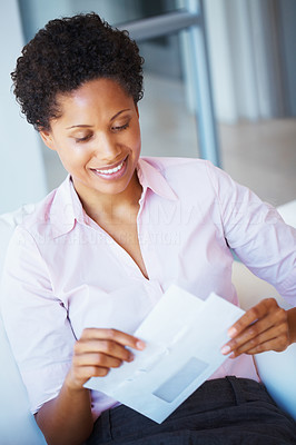 Buy stock photo African American business woman sitting on couch and opening letter