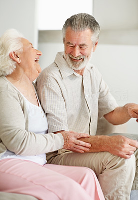 Buy stock photo Shot of an elderly couple laughing while using a laptop