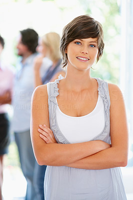 Buy stock photo Woman standing with arms crossed with people in background
